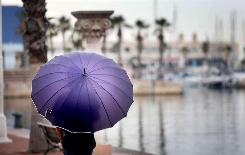 Un hombre se resguarda de la lluvia en el paseo mar�timo de Alicante. EFE/Archivo MANUEL LORENZO