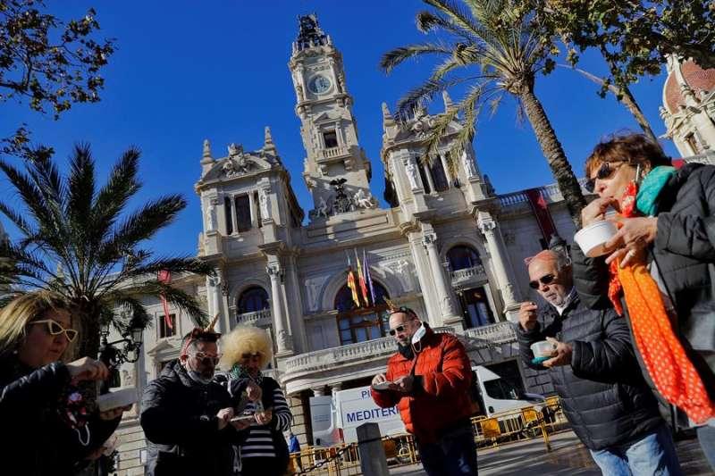 Un grupo de amigos adelanta la Nochevieja, ante las restricciones impuestas por la pandemia, y se han tomado las uvas al sonar las doce del mediodía en el reloj del Ayuntamiento de València. EFE/Manuel Bruque