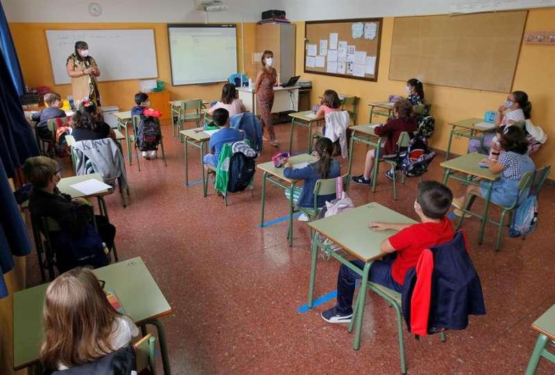 Alumnos en clase, con separación entre las mesas. EFE
