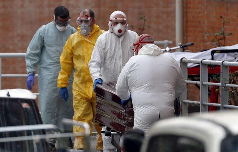 Trabajadores de una funeraria, protegidos, trasladan de una morgue a un fallecido por coronavirus en Madrid. EFE