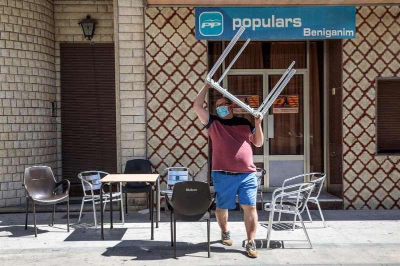 Un hombre recoge las sillas y mesas de la terraza de su negocio en la localidad valenciana de Benigànim (Valencia), en una imagen de ayer. EFE/ Biel Aliño