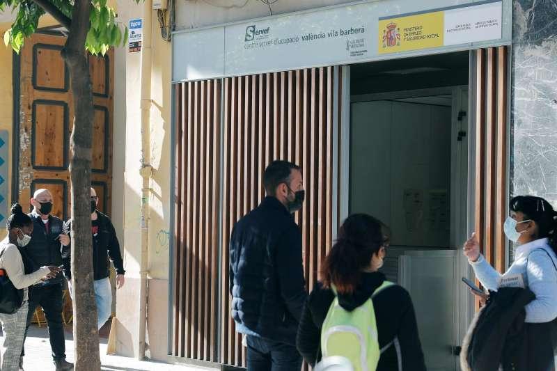 Varias personas aguardan ante una oficina del SERVEF.