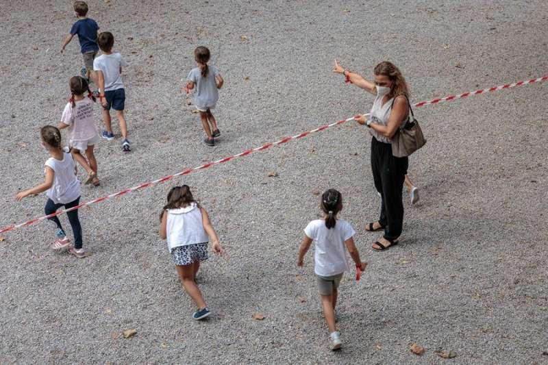 Varios niños y niñas se dirigen a la zona acotada para el recreo. EFE