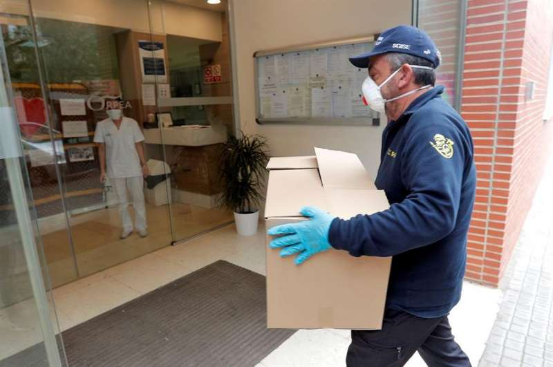 Un agente forestal reparte material sanitario en una residencia de ancianos en Valencia. EFE