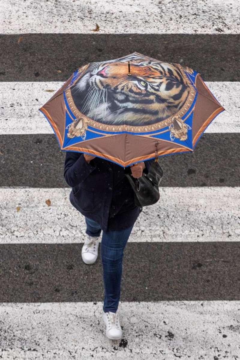 Una mujer se protege de la lluvia con paraguas. EFE