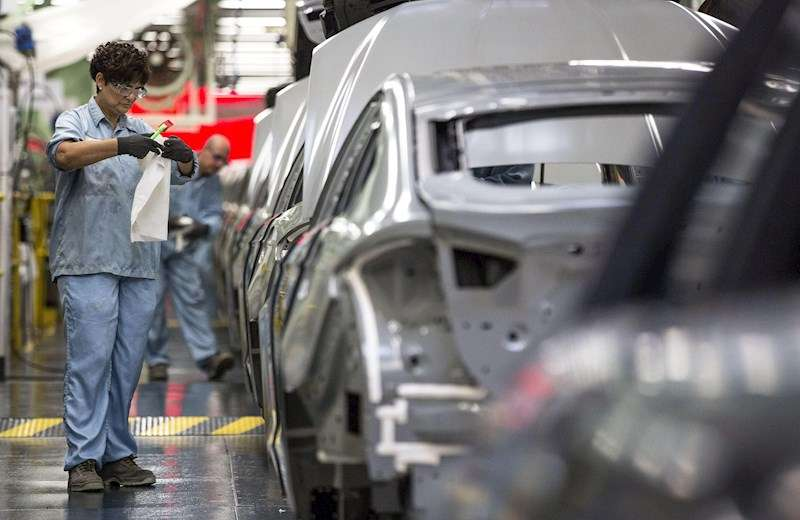 Varios trabajadores de la planta de pintura de Ford en Almussafes, revisan una carrocería antes de su paso por la zona de pintura. EFE