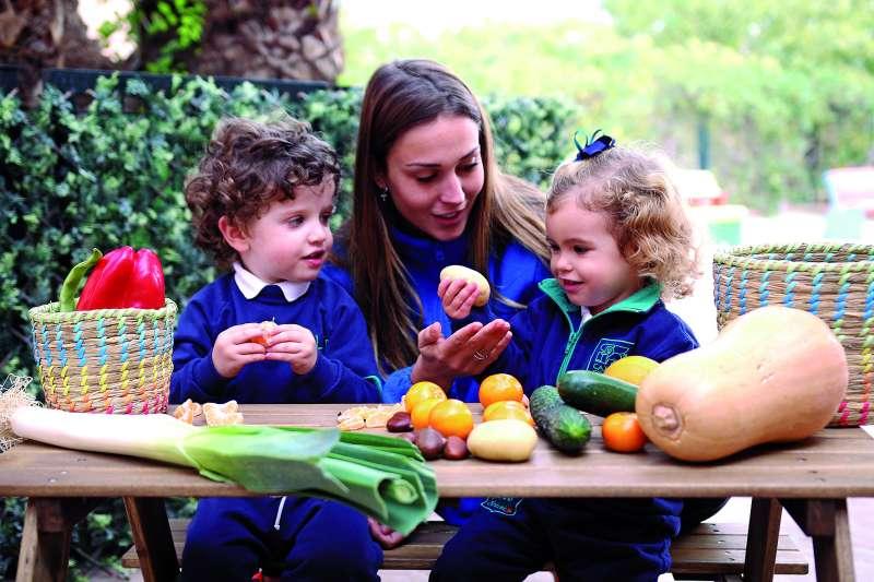 Alumnos de Baby Caxton junto con su profesora descubiriendo alimentos saludables. / EPDA