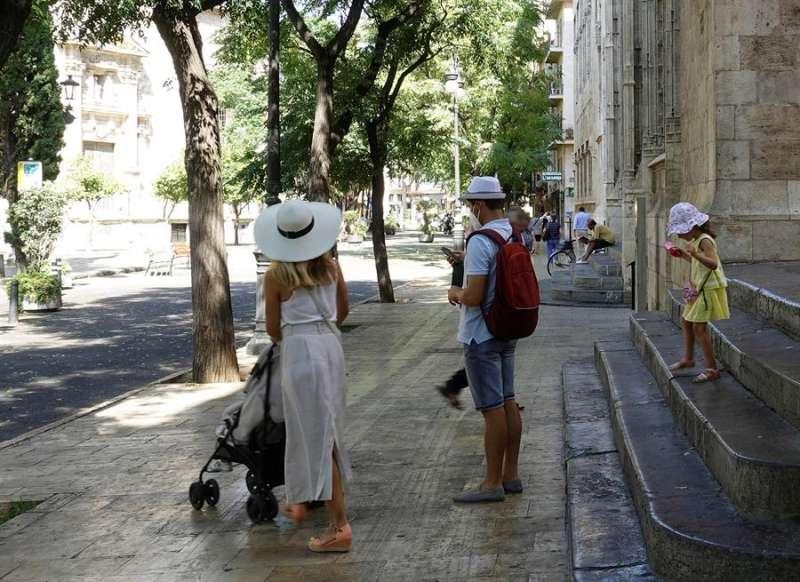 Una familia de turistas pasea junto al edificio de La Lonja, Patrimonio de la Humanidad, en el centro histórico de València. EFE
