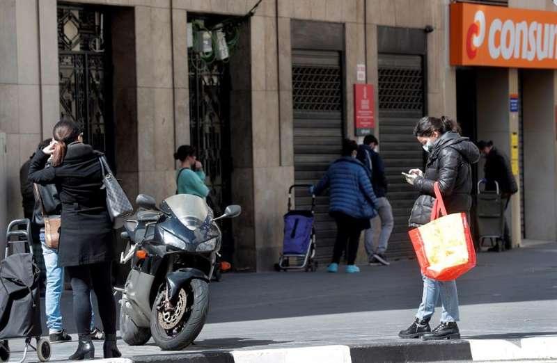 Varias personas guardan cola para realizar la compra en un supermercado de Consum. EFE