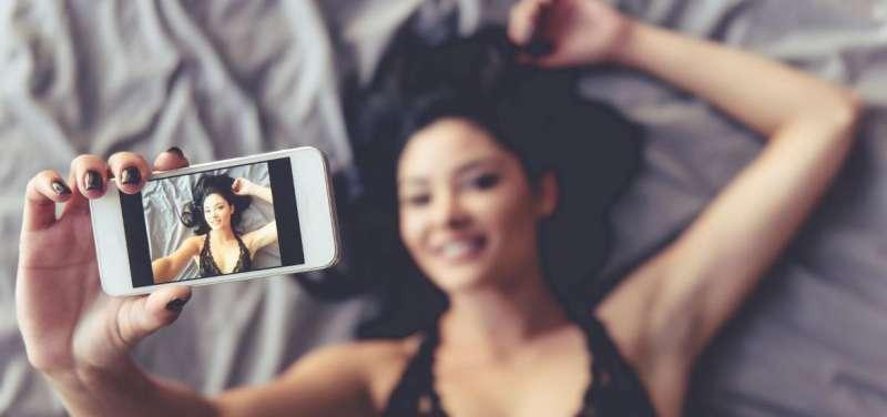 Una chica practica sexting con su teléfono móvil