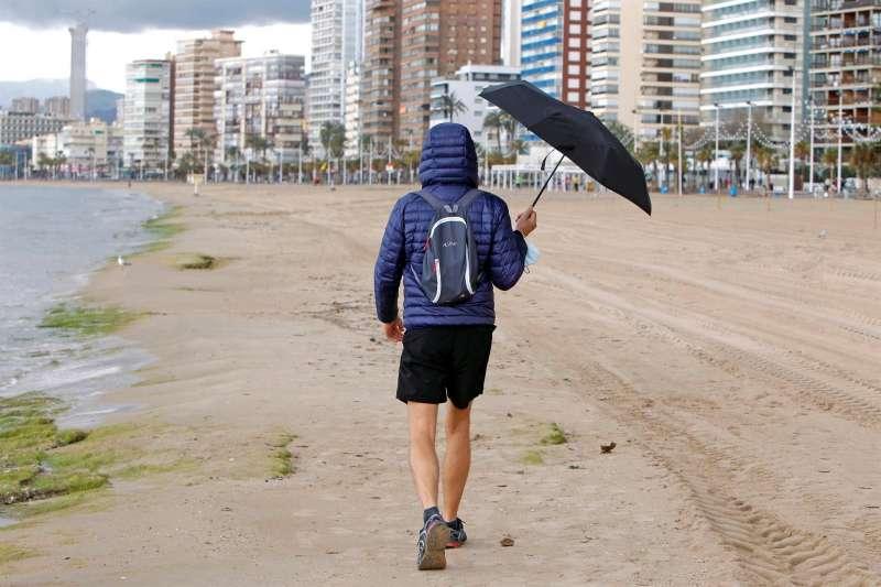 Una persona se protege de la lluvia con un paraguas mientras pasea por la playa de Levante de Benidorm.