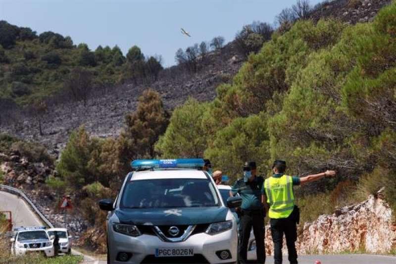 Varias patrullas de la Guardia Civil mantienen cortada la carretera que une La Llacuna con Lorxa debido al incendio que afecta a La Vall de la Gallinera. EFE/Natxo Francés