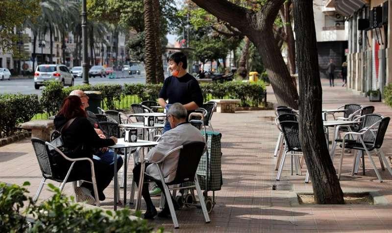 Un camarero, protegido con guantes y mascarilla, atiende a unos clientes en una terraza. EFE