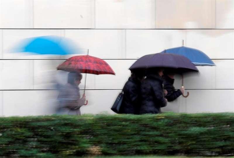 Varias personas se protegen de la lluvia. EFE/Kai Försterling/Archivo