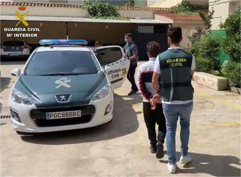 Uno de los detenidos, escoltado por un agente, en una imagen difundida por la Guardia Civil.