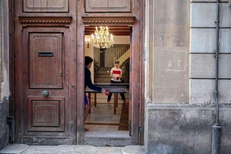 Dos personas juegan al tenis de mesa en el interior de su vivienda. EFE/Biel Aliño/Archivo
