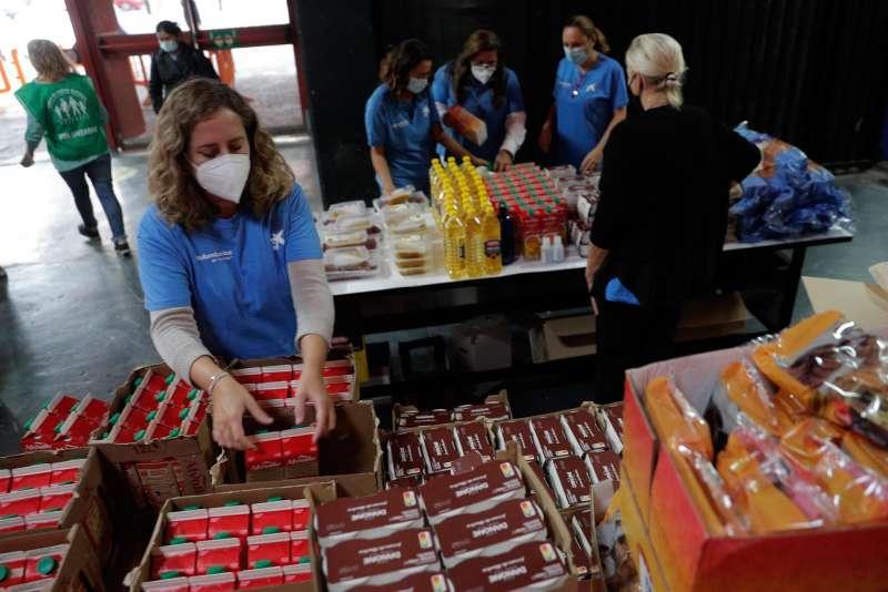 Varias personas recogen alimentos durante el reparto que ha realizado el Banco de Alimentos en el campo de Mestalla.