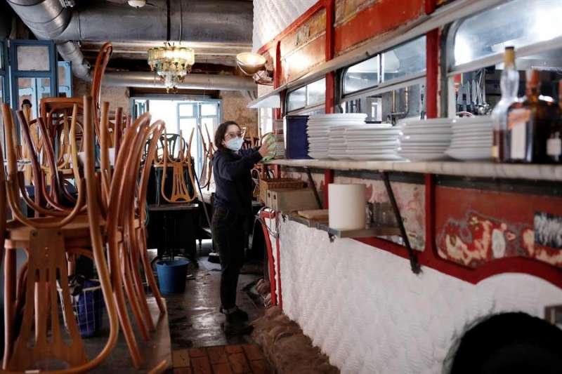 La encargada de un local realiza labores de limpieza y preparación para la reapertura. EFE