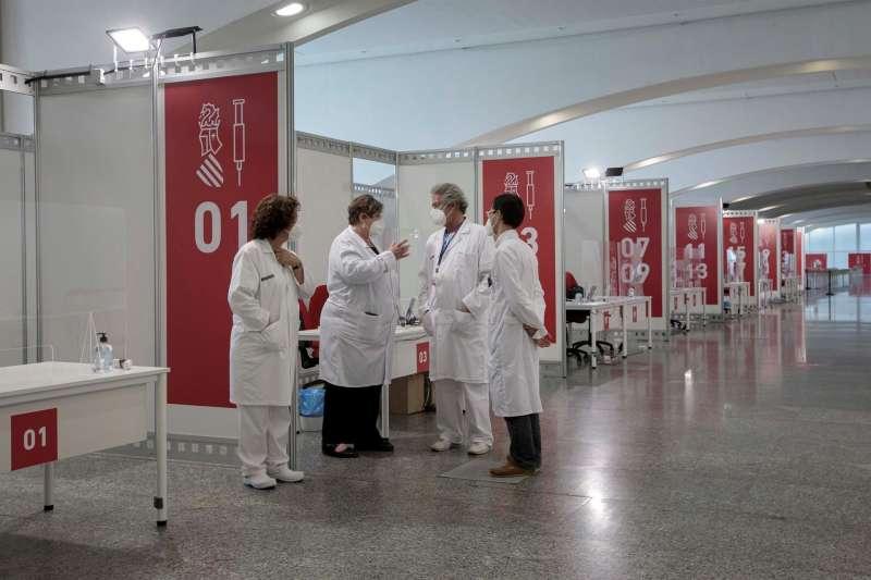 Varios sanitarios conversan este sábado en el punto de vacunación masiva de Valencia situado en la Ciudad de las Artes y las Ciencias.