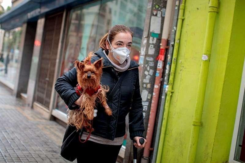 Una persona con mascarilla camina por la calle con un perro en brazos, en una imagen de estos días. EFE