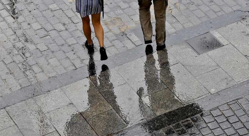 Dos personas caminan, este martes, protegidos por paraguas de la lluvia que ha caído en la ciudad de Valéncia. EFE