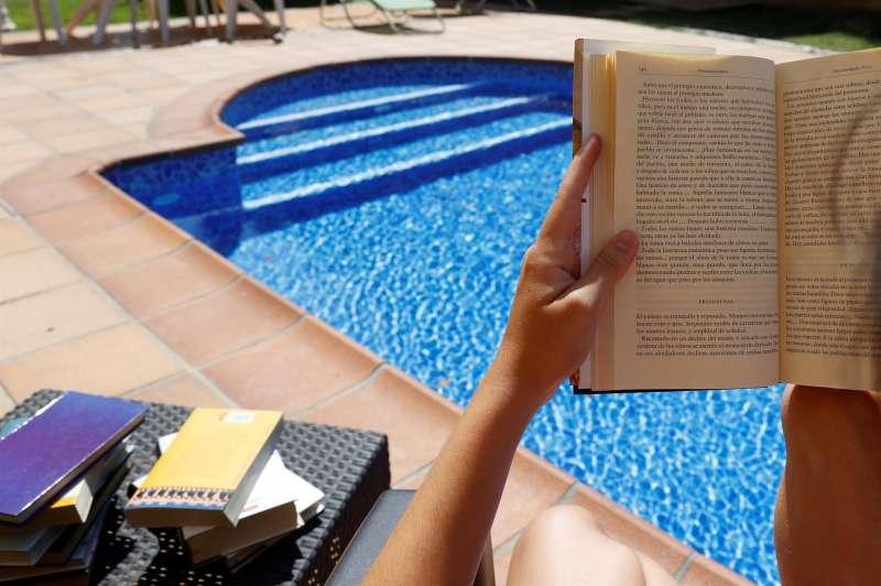 Una persona lee al borde de la piscina. EFE/J.J. Guillén/Archivo