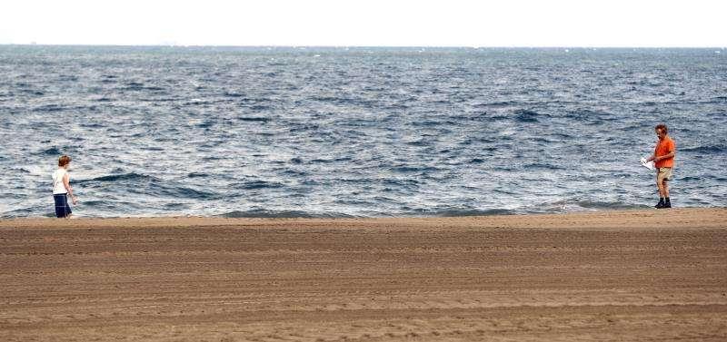 Dos personas pasean por una playa vacía. EFE/Archivo