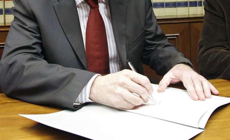 Imagen de archivo de una persona firmando documentos en una notaría. EFE
