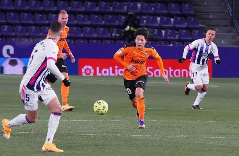 El centrocampista del Valencia Lee Kang-In (c) juega un balón ante Javier Sánchez, del Real Valladolid. EFE/R. García