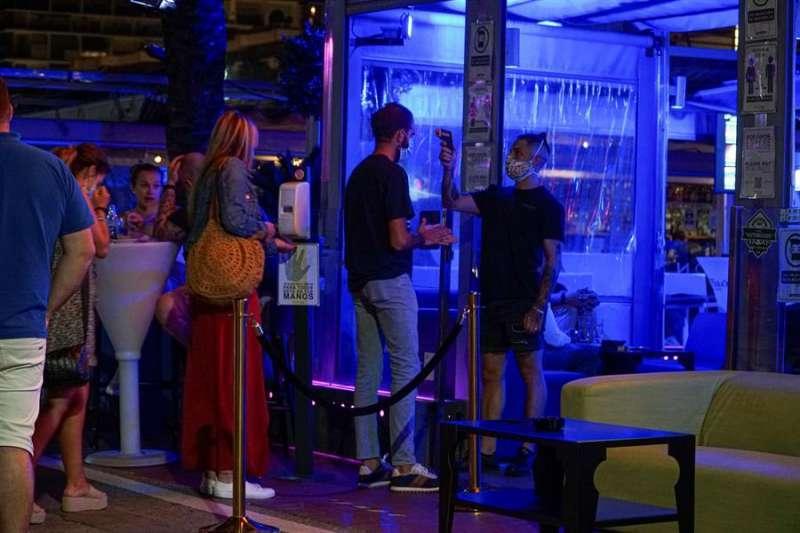 Un empleado toma la temperatura a un joven que hace cola para entrar en un pub. EFE