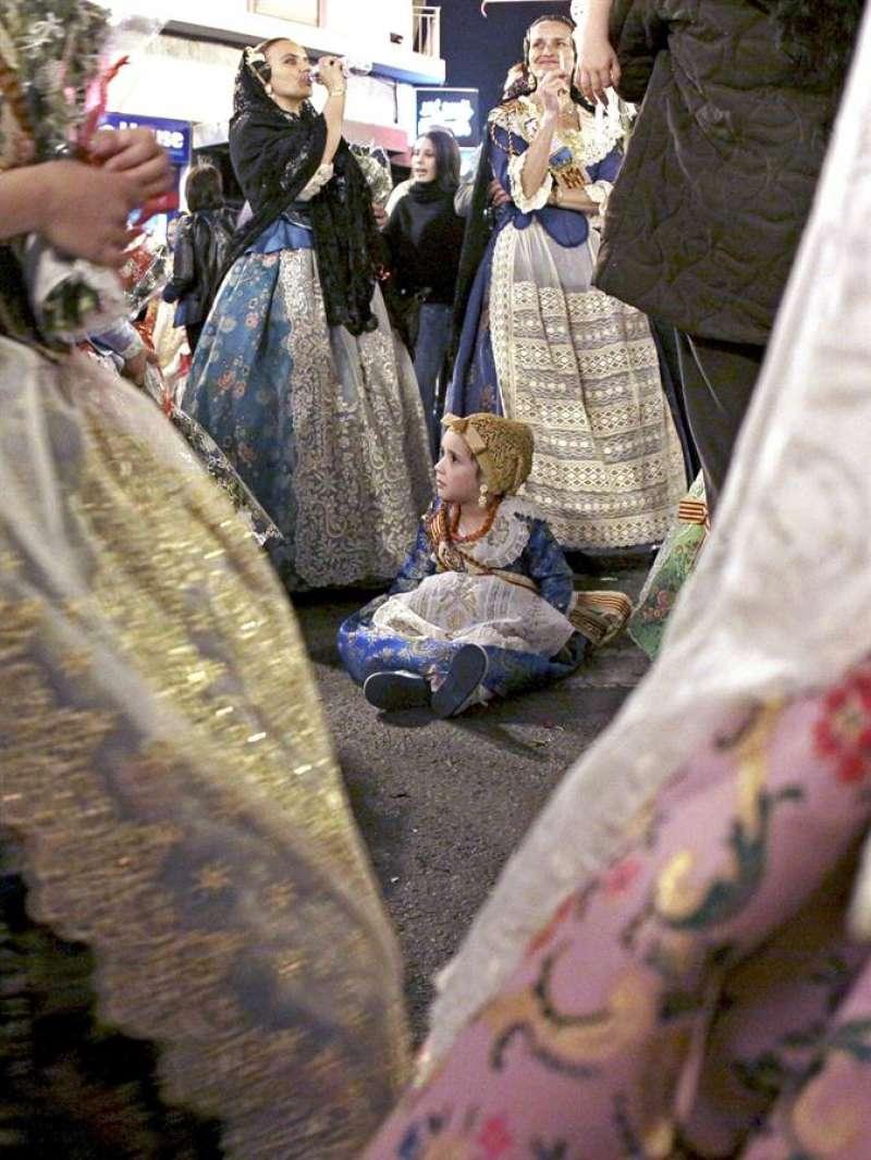 Una pequeña fallera descansa sentada en el suelo momentos antes de dirigirse hacia la ofrenda de flores a la patrona de la ciudad de Valencia. EFE