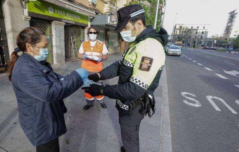 Un policía entrega mascarillas a una vecina. EFE