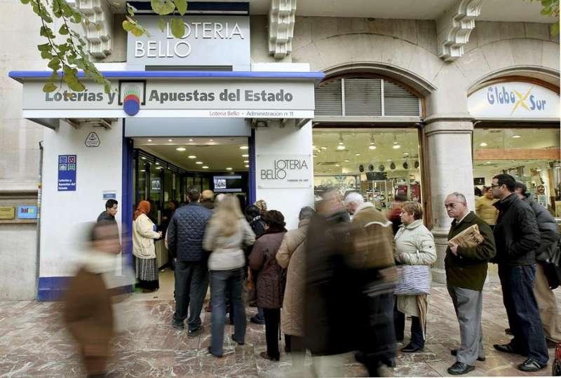 Numerosas personas hacen cola ante un céntrica Administración de Lotería de Valencia. EFE