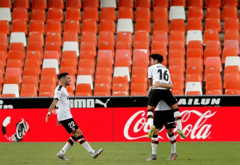 El centrocampista coreano del Valencia CF Kang-in Lee (d. arriba) celebra con Waas y Maxi Gómez (i) su gol, segundo del equipo ante el Real Valladolid, durante el partido correspondiente a la jornada 35º de Liga Santander que enfrentó a Valencia y Real Valladolid en el estadio de Mestalla. EFE/Kai Försterling