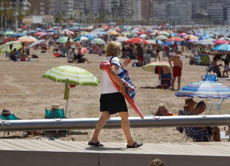 Una persona con mascarilla en la Playa de Levante de Benidorm