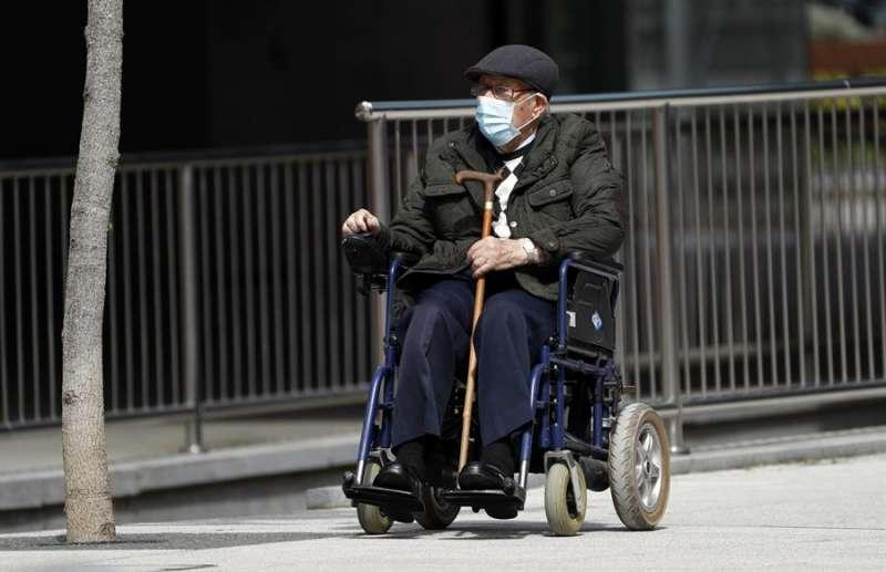 Un anciano protegido con mascarilla pasea por un parque. EFE/Archivo
