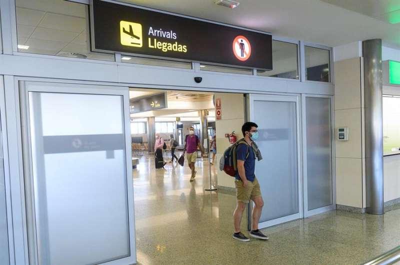 Viajeros en la zona de llegadas del aeropuerto. EFE/Pedro Puente Hoyos/Archivo