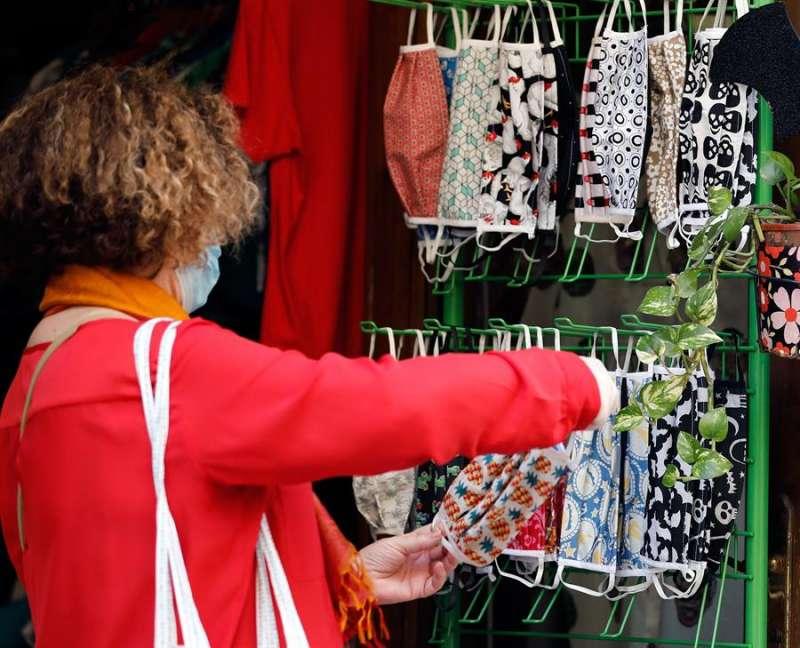 Una mujer elige entre distintos diseños de mascarillas en un comercio en Valencia. EFE/Archivo