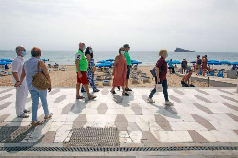 Un grupo de turistas paseando por la playa de Levante, en Benidorm. EFE/MORELL/Archivo