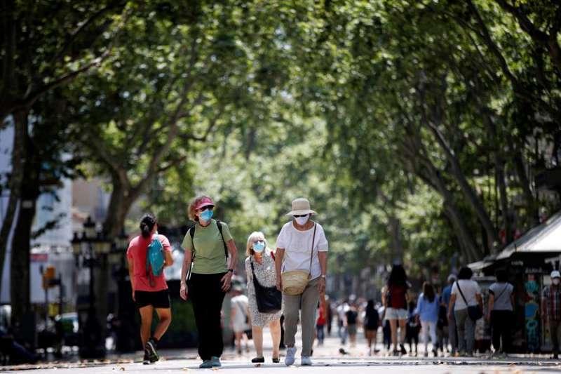 Varias personas caminan por la calle con mascarilla. EPDA