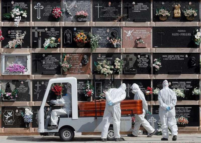 Imagen de archivo del personal del cementerio del Cabañal transportando un féretro en un entierro durante la pandemia. EFE